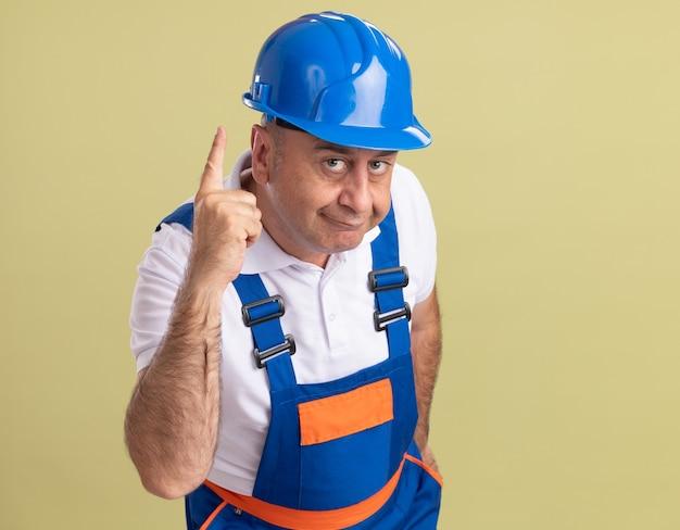 Tevreden volwassen bouwersmens in uniform wijst op olijfgroen