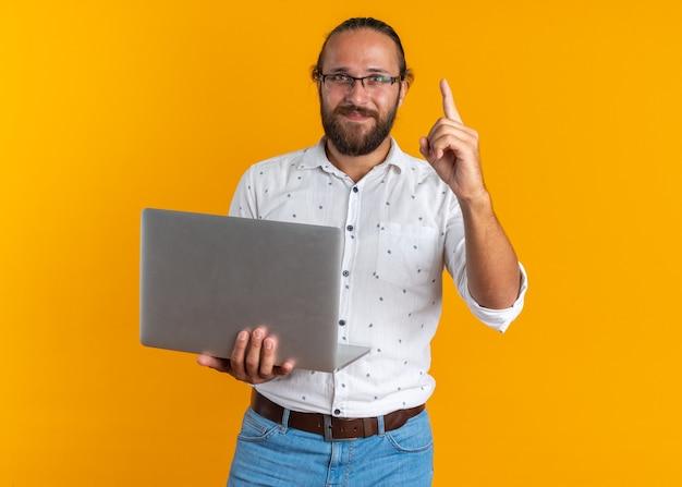 Tevreden volwassen knappe man met een bril die een laptop vasthoudt en naar een camera kijkt die omhoog wijst, geïsoleerd op een oranje muur