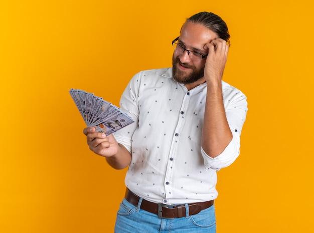 Tevreden volwassen knappe man met een bril die zijn hoofd krabt en naar geld kijkt dat op een oranje muur is geïsoleerd