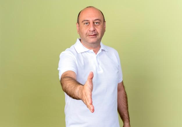 Tevreden volwassen man die hand uitstak die op olijfgroene muur wordt geïsoleerd