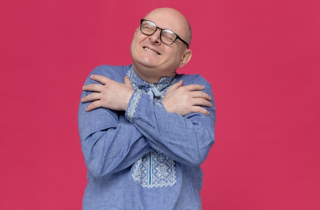Tevreden volwassen man in blauw shirt met een bril die zichzelf knuffelt