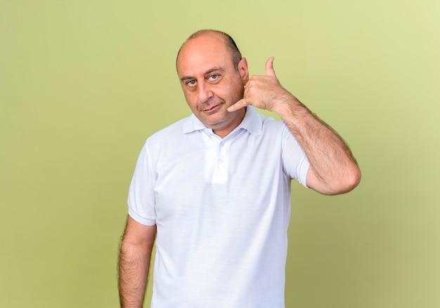 Tevreden volwassen man met telefoongesprek gebaar geïsoleerd op olijfgroene achtergrond