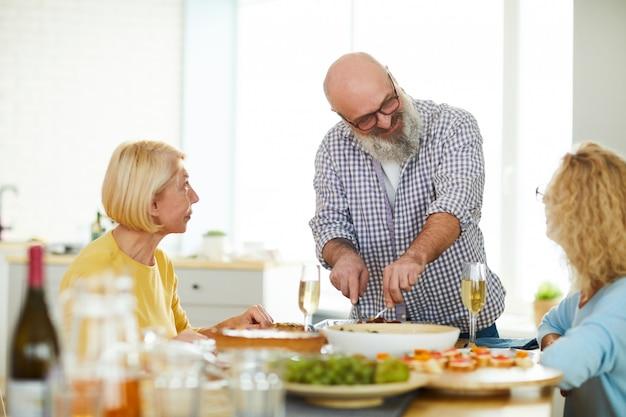Tevreden volwassen man snijden vlees voor gasten