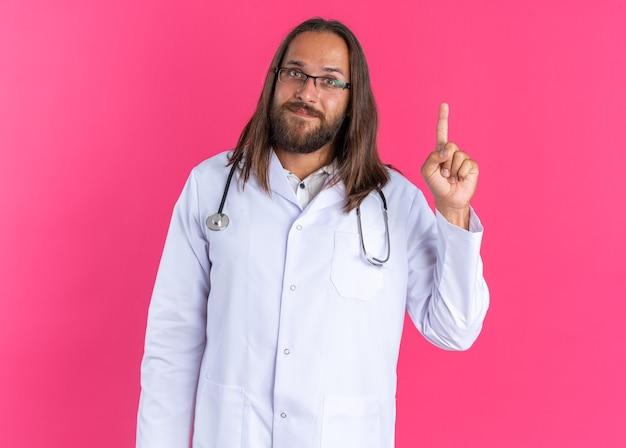 Tevreden volwassen mannelijke arts die een medisch gewaad en een stethoscoop draagt met een bril die naar de camera kijkt die omhoog wijst op een roze muur
