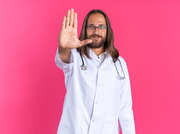 Tevreden volwassen mannelijke arts die een medisch gewaad en een stethoscoop draagt met een bril die naar de camera kijkt en een stopgebaar doet dat op een roze muur is geïsoleerd
