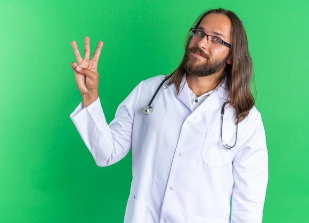 Tevreden volwassen mannelijke arts met een medisch gewaad en een stethoscoop met een bril die naar een camera kijkt met drie met de hand geïsoleerd op een groene muur