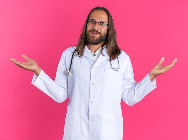 Tevreden volwassen mannelijke arts met een medisch gewaad en een stethoscoop met een bril die naar een camera kijkt met lege handen geïsoleerd op een roze muur