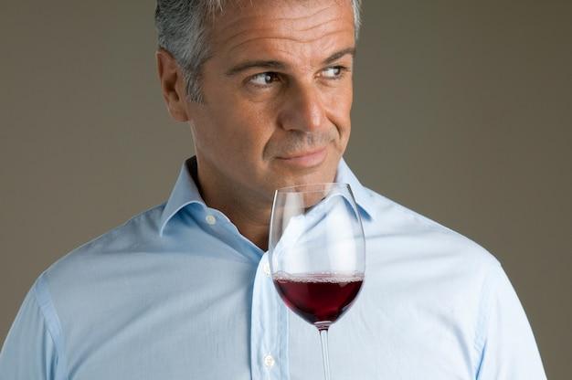 Tevreden volwassen sommelier ruikt naar een glas rode wijn