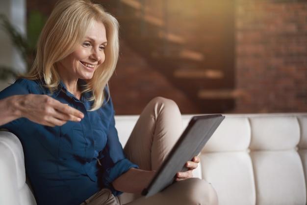 Tevreden volwassen vrouw die lacht terwijl ze een digitale tablet-pc gebruikt, ontspannen op een bank thuis in de