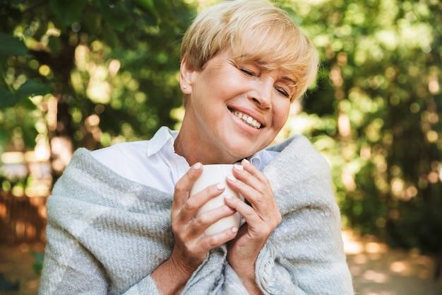 Tevreden volwassen vrouw gewikkeld in een deken