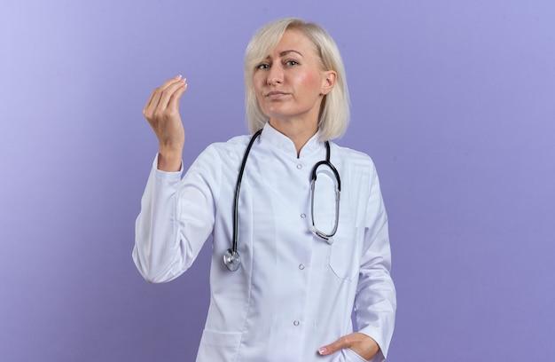 Tevreden volwassen vrouwelijke arts in medisch gewaad met stethoscoop die doet alsof ze iets vasthoudt dat op een paarse muur is geïsoleerd met kopieerruimte