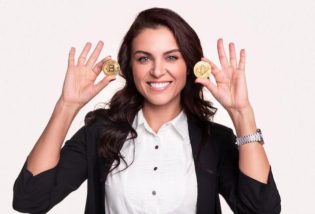 Tevreden volwassen zakelijke dame in formele outfit die gouden bitcoin-munten toont en kijkt terwijl ze de cryptocurrency-service vertegenwoordigt