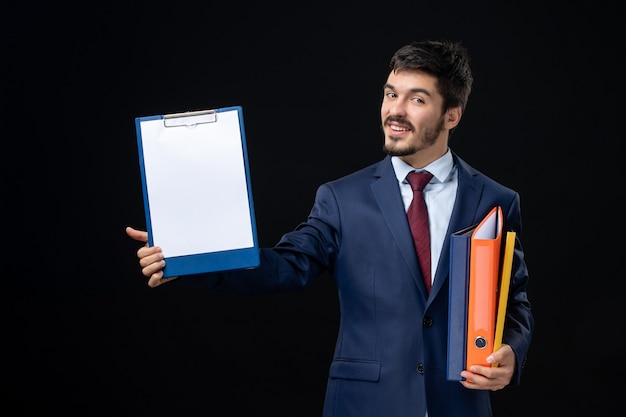 Tevreden volwassene in pak die verschillende documenten vasthoudt en een ervan op een geïsoleerde donkere muur laat zien