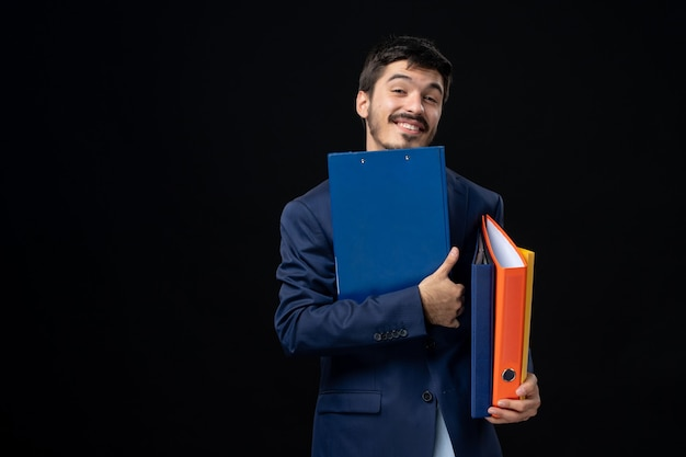 Tevreden volwassene in pak met verschillende documenten en poseren op geïsoleerde donkere muur