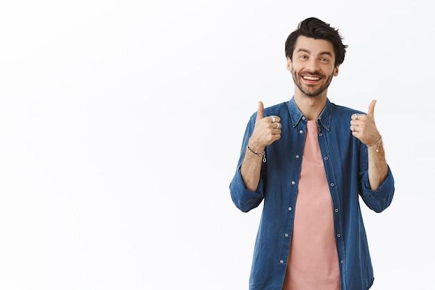 Tevreden, vriendelijke knappe blanke man in casual outfit die duimen omhoog laat zien als iets goeds beoordeelt, glimlacht en instemmend knikt, positieve feedback geeft, denkt dat iets uitstekend is
