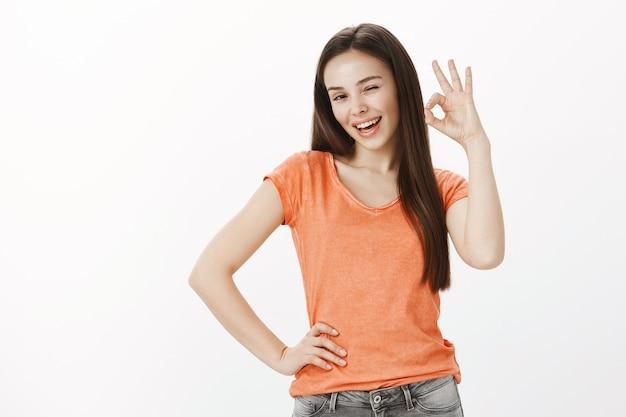 Tevreden vrolijk meisje, mooie vrouw met goedkeuringsgebaar, oké of goed, garantie voor kwaliteit, zoals idee