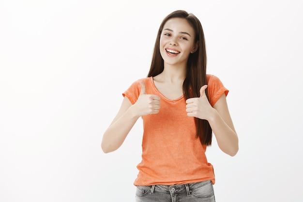 Tevreden vrolijk meisje, mooie vrouw met goedkeuringsgebaar, thumbs-up, garantie voor kwaliteit