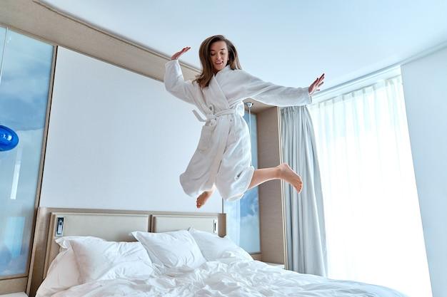 Tevreden vrolijke grappige vrouw in badjas springen op het bed in een hotelkamer tijdens een gelukkig moment. je goed voelen en genieten van het levensconcept. gemakkelijke levensstijl