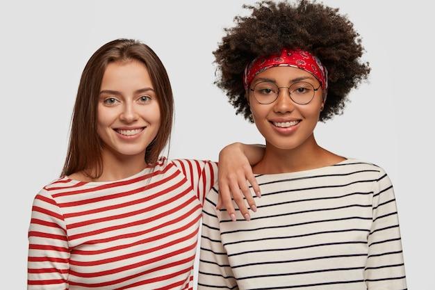 Tevreden, vrolijke vrouwen van verschillende rassen, voelen zich gelukkig door grappige praatjes, glimlachen breed, dragen soortgelijke gestreepte truien, geïsoleerd over een witte muur, hebben een goed humeur en plezier. multiculturele meisjes