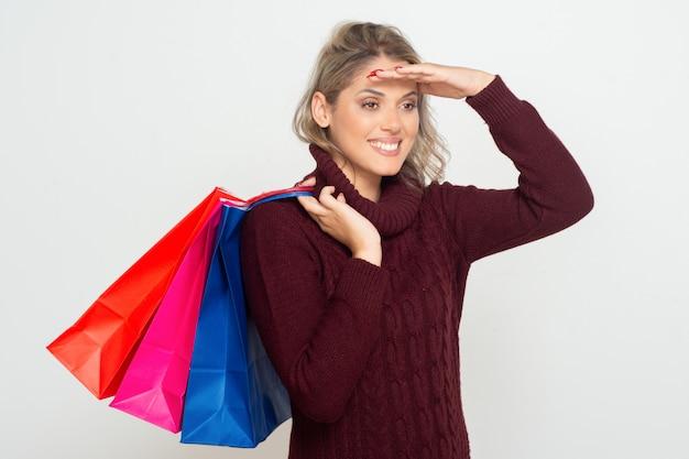 Tevreden vrouw die met het winkelen zakken opzij kijken