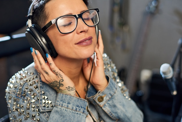 Tevreden vrouw die van muziek in studio genieten