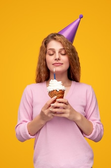 Tevreden vrouw die wens op verjaardags blazende kaars maakt Premium Foto