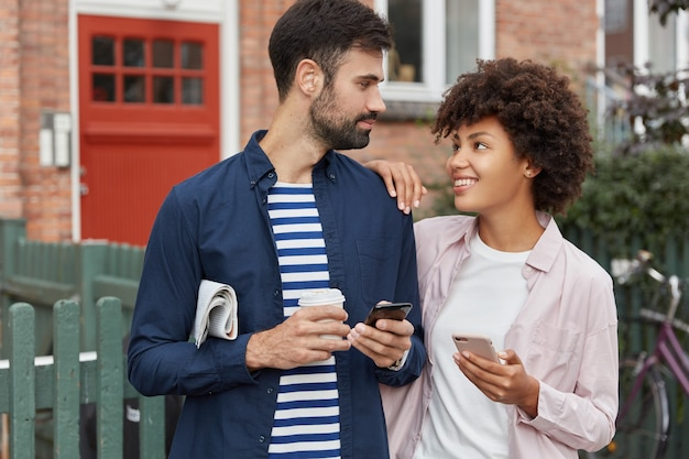 Tevreden vrouw en haar vriend uit verschillende landen wisselen telefoonnummers uit