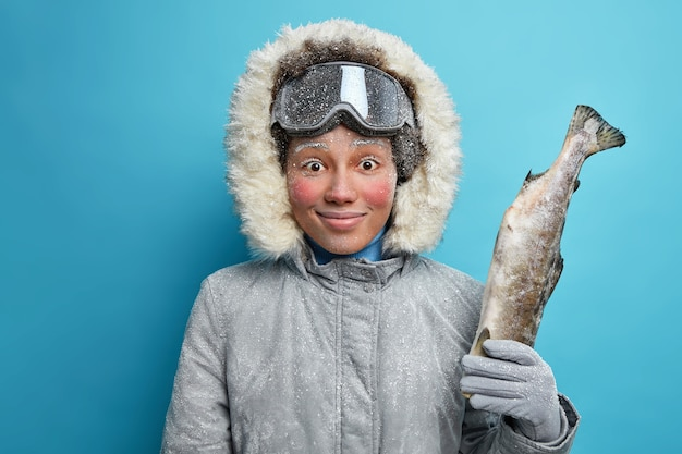 Tevreden vrouw geniet van wintervissen glimlacht blij en houdt grote gevangen vis vast ziet er verrassend uit: draagt een grijze jas met capuchon besteedt vrije tijd bij koud winterweer heeft een rood bevroren gezicht