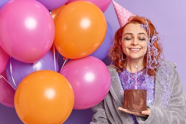 Tevreden vrouw heeft feeststemming houdt opgeblazen kleurrijke ballonnen vast en verjaardagstaart sluit ogen met tevredenheid glimlach drukt aangenaam oprechte emoties uit blij gefeliciteerd met verjaardag te accepteren
