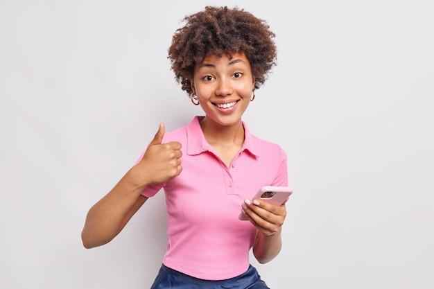Tevreden vrouw houdt mobiele telefoon vast maakt als gebaar houdt duim omhoog zegt ja en beveelt nieuwe applicatie aan gekleed in vrijetijdskleding geïsoleerd over witte muur