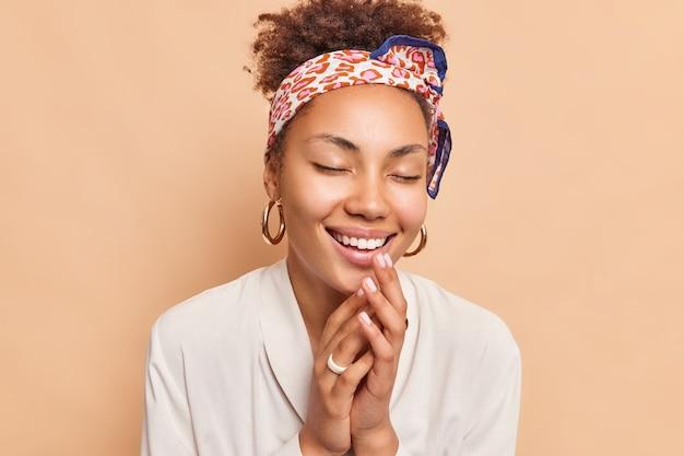 Tevreden vrouw houdt ogen gesloten glimlacht aangenaam drukt handpalmen tegen elkaar herinnert zich iets aardigs draagt hoofdband wit overhemd drukt oprechte gevoelens uit geïsoleerd over bruine muur