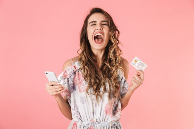 Tevreden vrouw in jurk met smartphone en creditcard, geïsoleerd op roze