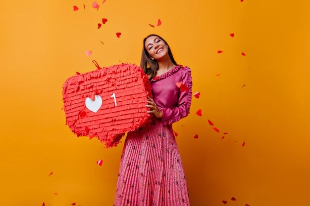 Tevreden vrouw in roze outfit lachen. aanbiddelijk kaukasisch meisje in lange rok die zich op gele muur bevindt.