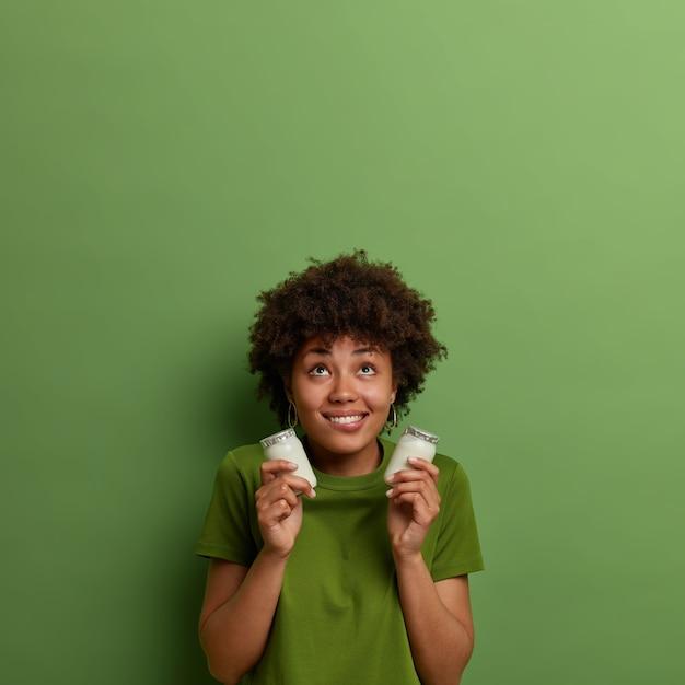 Tevreden vrouw met donkere huid houdt potten met biologische natuurlijke yoghurt, ingrediënt voor het bereiden van het ontbijt, geconcentreerd boven, hoed brede glimlach, draagt groen t-shirt. mensen en gezond voedingsconcept