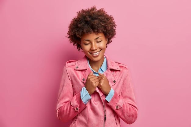Tevreden vrouw met donkere huid roept mooie herinneringen op, houdt handen op jas, sluit ogen en lacht aangenaam