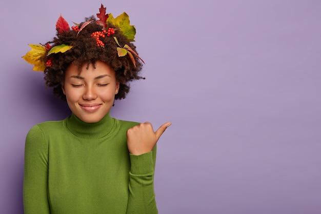 Tevreden vrouw met donkere huid sluit ogen van plezier, lacht zachtjes, wijst duim weg, draagt groene coltrui, demonstreert geweldige promo