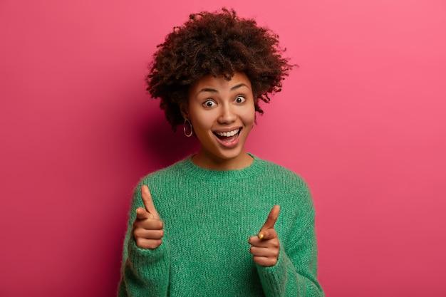 Tevreden vrouw met donkere huidskleur maakt vingerpistool pistool, wijst naar je, spreekt keuze uit, lacht aangenaam, draagt groene trui, geïsoleerd op roze muur, lacht vrolijk, feliciteert collega