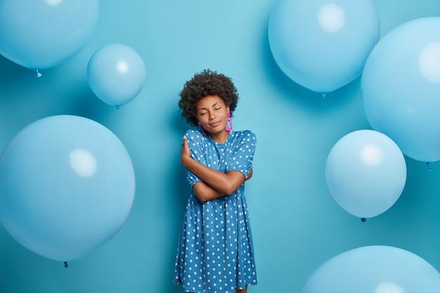 Tevreden vrouw met een donkere huid omhelst zichzelf en sluit de ogen van plezier, poseert met blauwe ballonnen