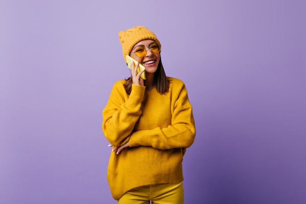 Tevreden vrouw met lang schouderhaar gelukkig tijdens een gesprek met de beste vriend via de smartphone. echt glimlachende student in stijlvolle hoed en gele outfit wil een foto maken op geïsoleerde paars