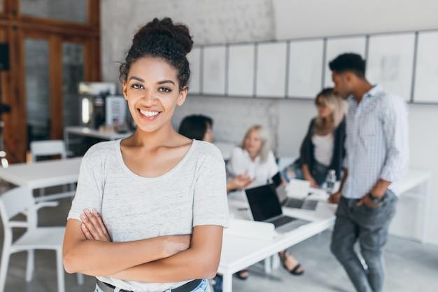 Tevreden vrouw met lichtbruine huid poseren met gekruiste armen en glimlachen, terwijl mensen achter haar aan het werk zijn. binnenportret van vermoeide studenten met laptop en afrikaans krullend meisje.