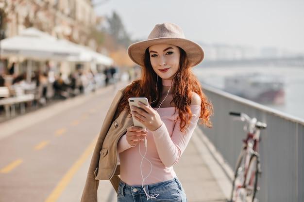 Tevreden vrouw met sluwe glimlach die telefoon houdt dichtbij straatrivier