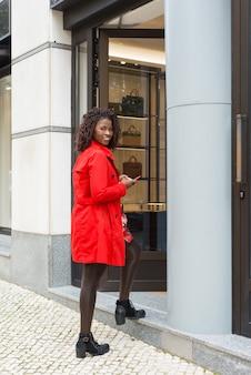 Tevreden vrouw met smartphone die winkel ingaat