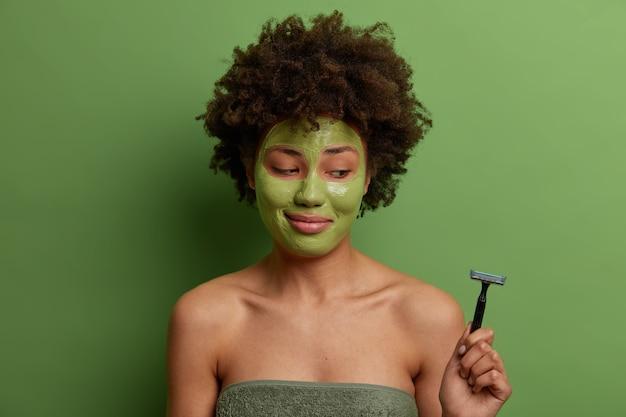 Tevreden vrouw past thuis een hydraterend schoonheidsmasker toe, wil een schone, perfecte huid, houdt een scheermes vast, heeft een hygiënische behandeling, staat in een handdoek gewikkeld die over een groene muur wordt geïsoleerd. schoonheidsprocedures