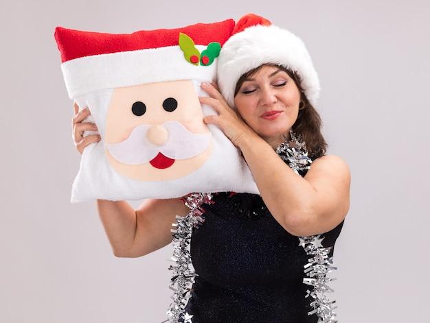 Tevreden vrouw van middelbare leeftijd dragen kerstmuts en klatergoud slinger rond de nek met kerstman kussen hoofd aanraken met het met gesloten ogen geïsoleerd op witte achtergrond