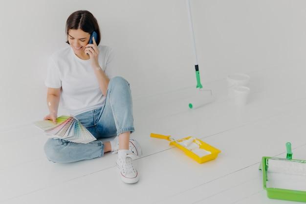 Tevreden vrouwelijke ontwerper bespreekt ideeën via smartphone
