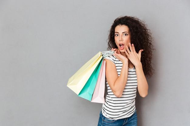Tevreden vrouwelijke shopaholic die met alle aankopen en pakketten wordt opgewekt die vrije dag in winkelcomplex doorbrengen