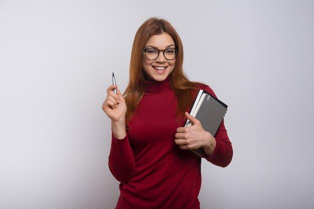 Tevreden vrouwelijke student met leerboeken en pen