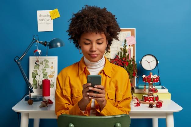 Tevreden vrouwelijke student neemt pauze van autodidact, gebruikt mobiel om online te chatten, bladert door applicatie, stuurt sms, controleert mail via wifi, zit op stoel bij werkplek, blauwe muur.