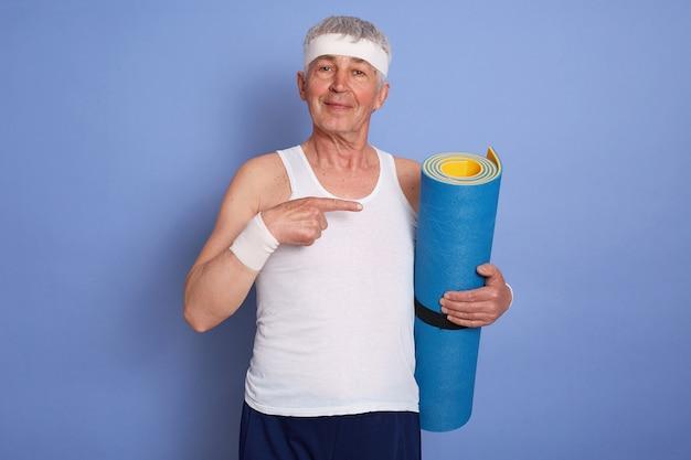 Tevreden witharige man met yogamat geïsoleerd poseren, wijzend met wijsvinger opzij, mouwloos t-shirt, haarband en polsbandje dragen.