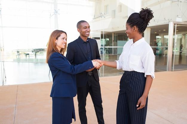 Tevreden zakelijke partners die handdruk maken